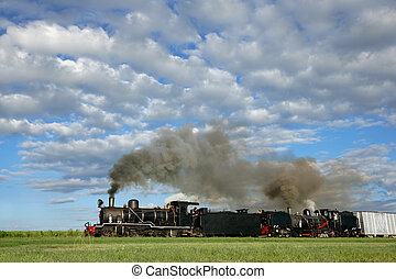 Two vintage steam locomotives with billowing smoke and steam pulling railroad cars