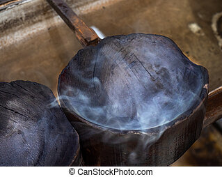 Steam rises from a wooden mold to form melted glass. Glass blowing studio