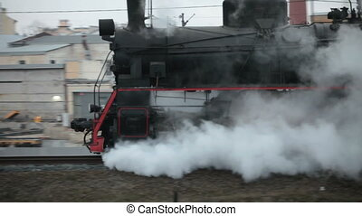 steam train in clouds of smoke passes by - Sooty steam train...