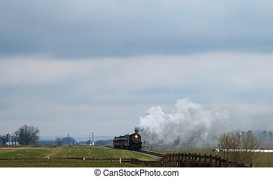 A steam train approaching in the distance surrounded by a big ominous sky and a rural farmland landscape.