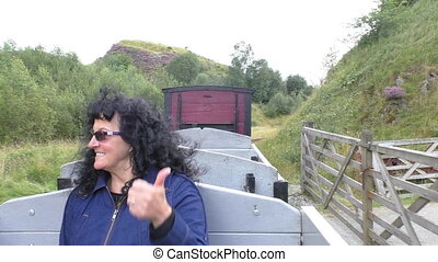 Steam train passenger enjoying a ride - Dark curly hair...