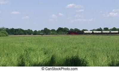 Steam train running in rural landscape - wide shot - Steam...