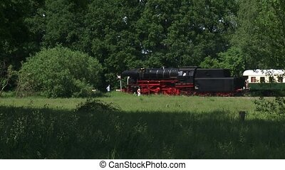 Steam train whistles and passes railway crossing - Steam...