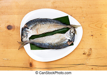 steam with mackerel in white dish on wood table
