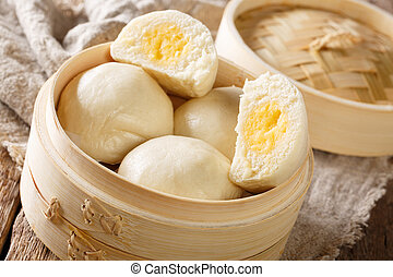 Steamed Chinese bun with custard cream stuff filling in...