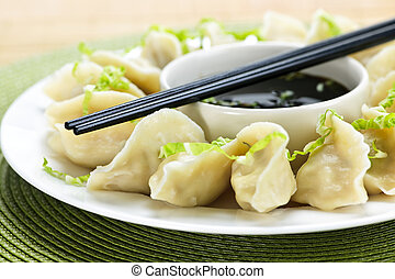 Steamed dumplings and soy sauce - Closeup on plate of ...