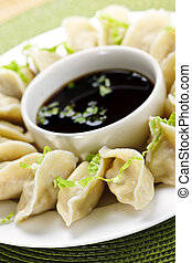 Steamed dumplings and soy sauce - Closeup on plate of...