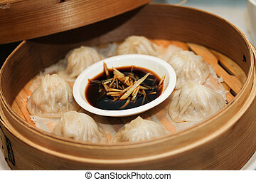 Steamed dumplings or dim sum with sauce in bamboo stew