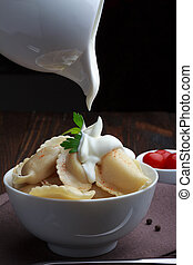 Steamed meat dumplings, pouring sour cream, traditional pelmeni or varenyky dish