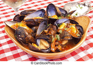 Plate of steamed mussels with tomato and white wine sauce or marinara sauce and a glass of white wine in the background