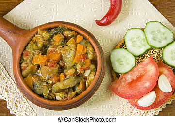 Steamed vegetables in a pan and chopped fresh vegetables on a white napkin