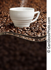 steaming cup on background of coffee beans with copy space