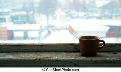 Steaming earthenware cup on old wooden window sill