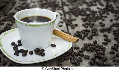 A steaming hot cup of coffee on wood background