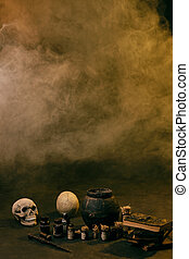 Steaming pot against a black studio background. There are jars with ingredients for a potion, skulls, magic wand and books with spells around it.