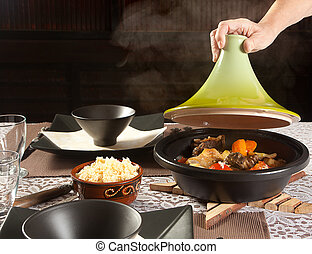 Steaming tajine food - Hand lifting the lid of a steaming...