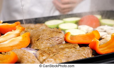 Steaming vegetables and meat on a grill