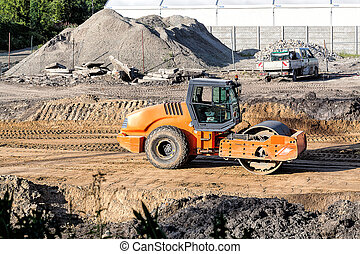 Steamroller - An orange steamroller working on a ...