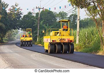 Steamroller are crushed the asphalt road.