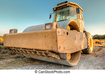 Closeup of steamroller in a suggestive construction site at dawn. Concept of work in progress.