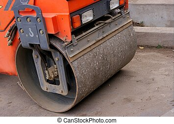 Front of a small, orange, parking steamroller