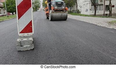 Steamroller is spreading hot asphalt