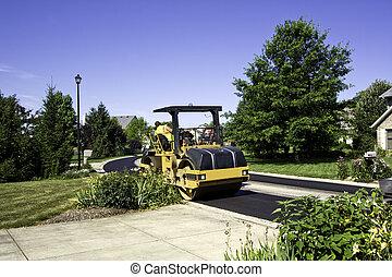 Steamroller smooths new asphalt in a residential ...
