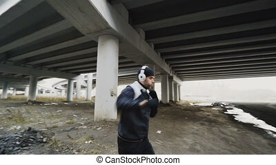 Stedicam shot of boxer man in headphones doing boxing...