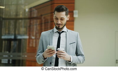 Stedicam shot of cheerful businessman using smartphone and...