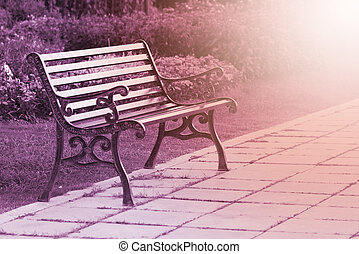 steel bench in park with sunrise