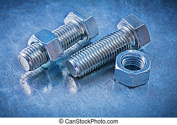 Steel bolts with screw-nuts on metallic background construction