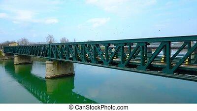 Green metal bridge with train tracks crosses the river
