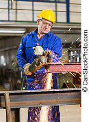 Steel construction worker cutting metal with angle grinder -...
