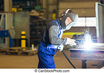 Steel construction worker welds metal parts - Steel...
