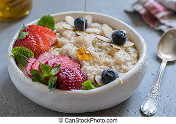 Steel cut oatmeal porridge with strawberry and blueberry for breakfast