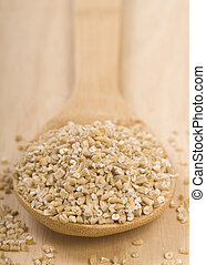 Steel cut oats on a wooden spoon - Fresh grits on a wooden ...