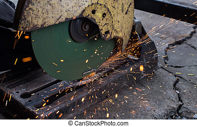 Closeup cutting process of metal material with sparks, industrial