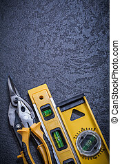Steel cutter gripping tongs construction level on black background.