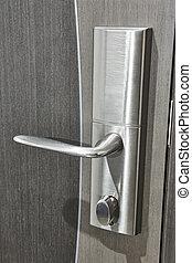 Steel door knob with lock on a grey wooden door