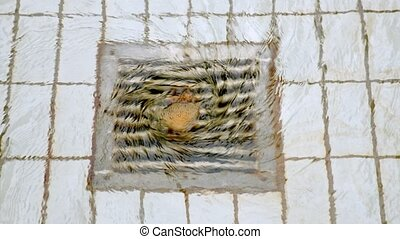 Steel drain on tiled floor with water whirling closeup