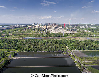 Steel factory with smokestacks at sunny day. Metallurgical plant. steelworks, iron works. Heavy industry in Europe. Air pollution from smokestacks, ecology problems. Industrial landscape. View from above.