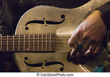 Macro photo with selective focus on the steel guitar, slow shutter with slight movement of hand.