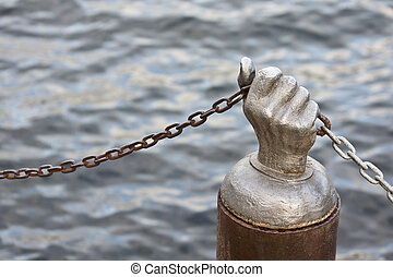 Steel Hand Holding Chain against the water - Steel hand...