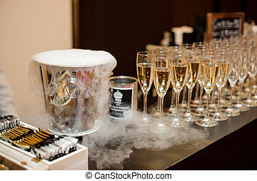 Steel ice bucket and set of glasses filled with champagne