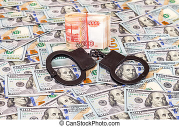 Steel police handcuffs lying on the background of american dollars with folded stack of banknotes of russian roubles