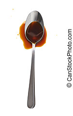 Steel spoon in a puddle of worchester sauce isolated over...