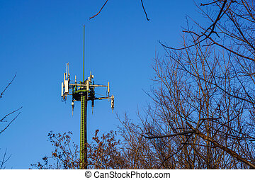 Steel telecommunication tower with antennas over blue sky and trees