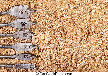 Steel wood drill bits arranged on sawdust. Carpentry accessories for mechanical drainage.