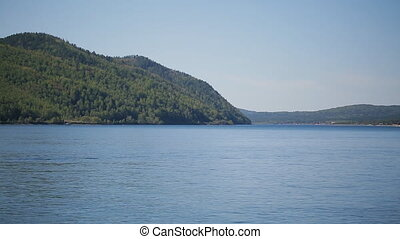 Steep bank of sea or lake with thick forest on a sunny day and blue sky.