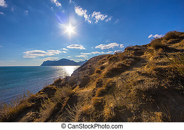 Steep grassy slope. Sea and mountains.